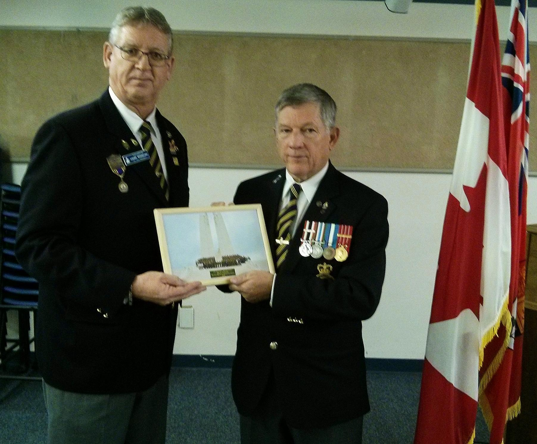 Branch 88 1st Vice President Andre Wesseling presents a photo to President Mike Ward at the October General Meeting. The photo of the Nijmegen March Canadian contingent was taken at the Vimy Memorial in France where Comrade Wesseling laid a wreath representing the Royal Canadian Legion. Andre was one of two Legion members selected from across Canada to participate in the Nijmegen March this year.