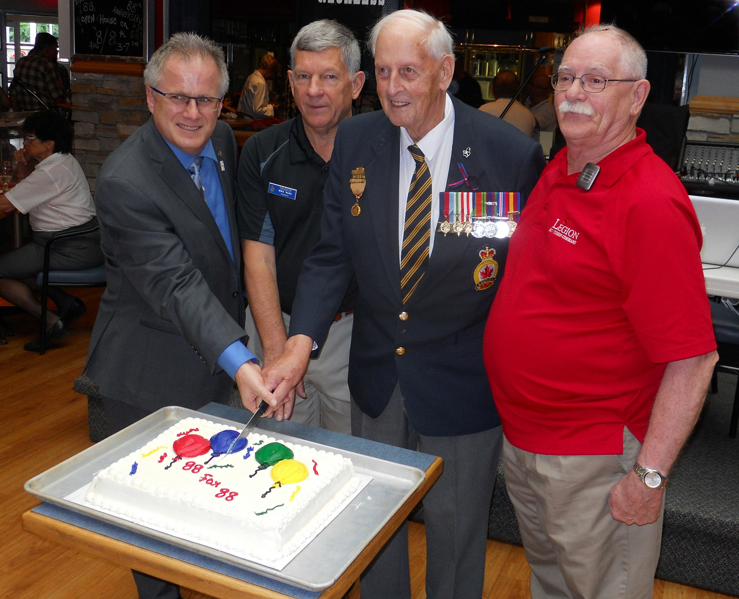 On August 8th, Branch 88 Maple Ridge celebrated 88 years of continuous service to our Veterans and the community. Cutting the anniversary cake at our well-attended Open House is (left to right) Marc Dalton MLA, Branch President Mike Ward, WWII Veteran Bill Mitchell and Legion New Westminster &Zone Commander Peter Dunford.