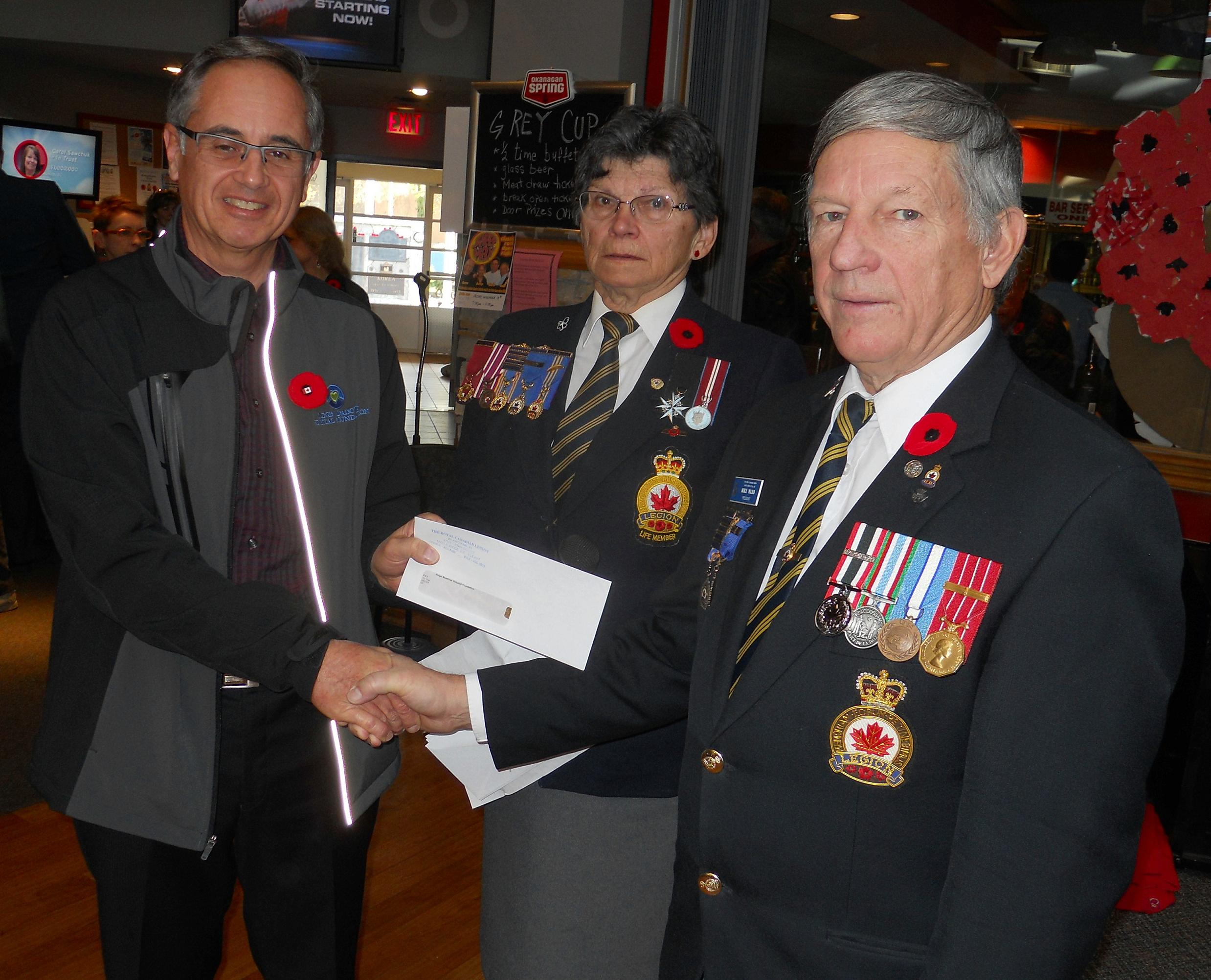 Branch President Mike Ward presents a cheque for $20,000.00 to Ridge Meadows Hospital Foundation board member Art Van Pelt at the Remembrance Day ceremonies.