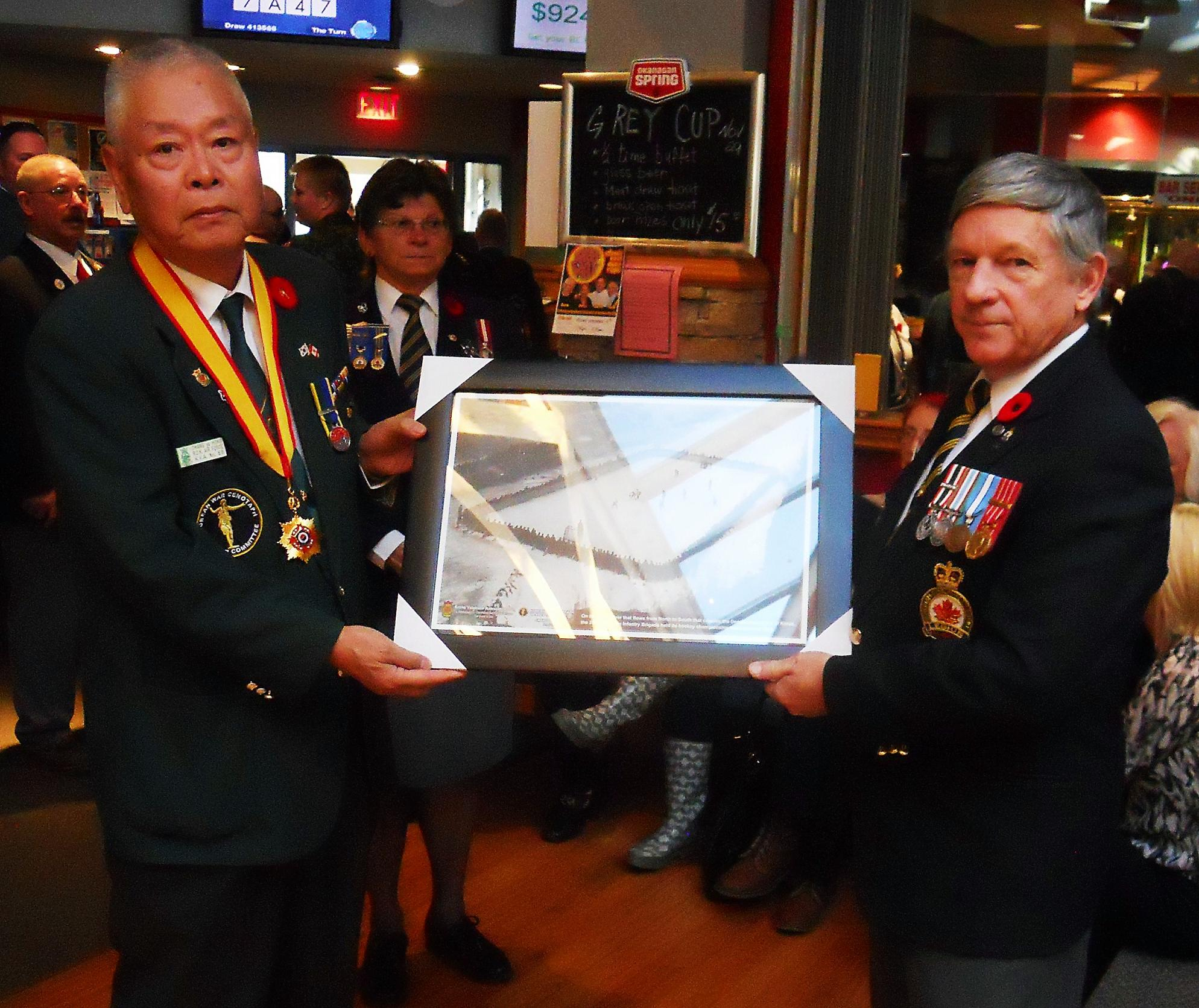 Chang Uy Hong, President of the Korean War Cenotaph Committee presented Branch President Mike Ward with a framed photograph of the famous hockey game played on the Imjin River in Korea in 1953 between the PPCLI and the Royal 22e Regiment.
